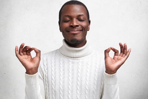 Jovem homem contente de pele escura mantém os olhos fechados e os dedos em sinal de mudra, tem uma expressão calma, tenta relaxar após um dia cansativo