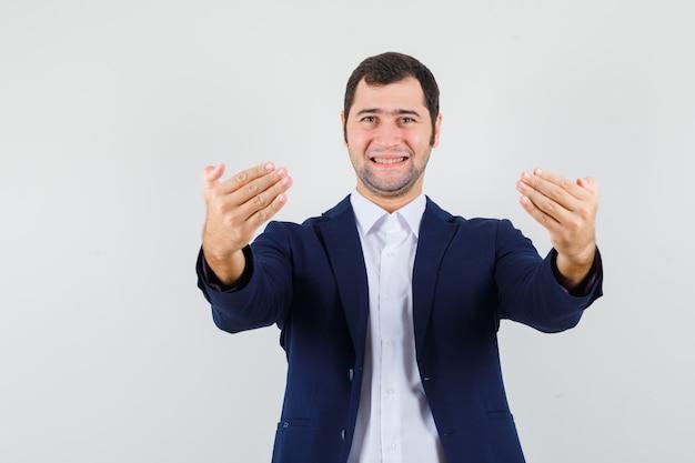 Jovem homem convidando para entrar em camisa, jaqueta e parecendo alegre