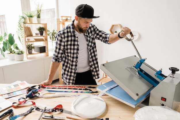 Jovem homem criativo imprimindo ou colando decoração em uma das peças de coleira para animais de estimação enquanto usa equipamento técnico