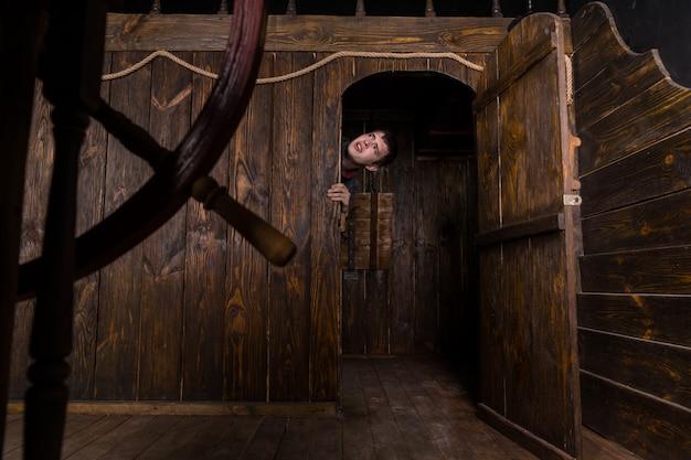 Jovem homem curioso espiando por dentro da porta da cabine de um antigo veleiro de madeira, pendurado na moldura da porta e parecendo aflito
