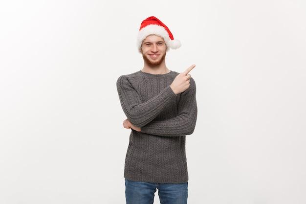 Jovem homem de barba em suéter gosta de brincar e apontar o dedo para o lado