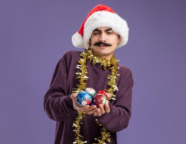 Jovem homem de bigode usando chapéu de papai noel com enfeites de natal ao redor do pescoço segurando bolas de natal com um sorriso cético em pé sobre a parede roxa