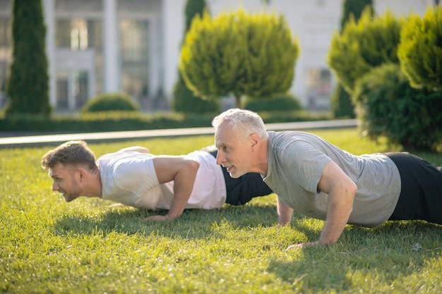 Jovem homem de cabelos castanhos e homem maduro de cabelos grisalhos fazendo flexões na grama