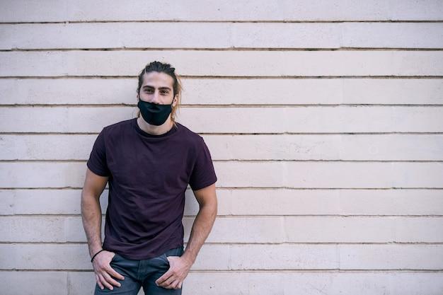 Jovem homem de cabelos compridos em uma parede enquanto usa uma máscara preta contra a pandemia de coronavírus