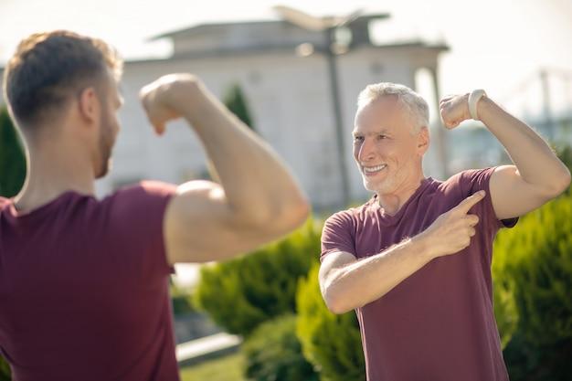 Jovem homem de cabelos grisalhos em pé, mostrando os bíceps um ao outro