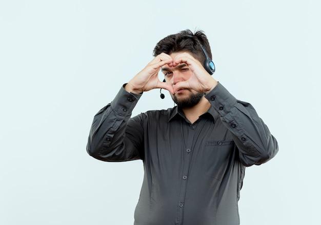Jovem homem de call center usando fone de ouvido, mostrando gesto de coração isolado no branco