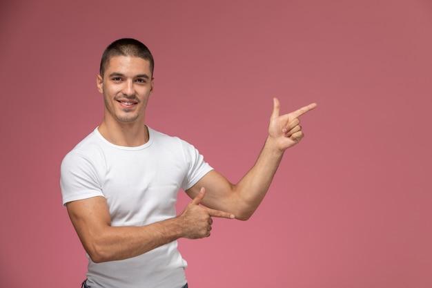 Jovem homem de camisa branca, de frente para a frente, posando com uma expressão apontando no fundo rosa