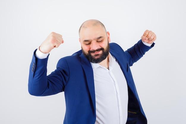 Jovem homem de camisa branca, jaqueta mostrando o gesto do vencedor e parecendo feliz, vista frontal.