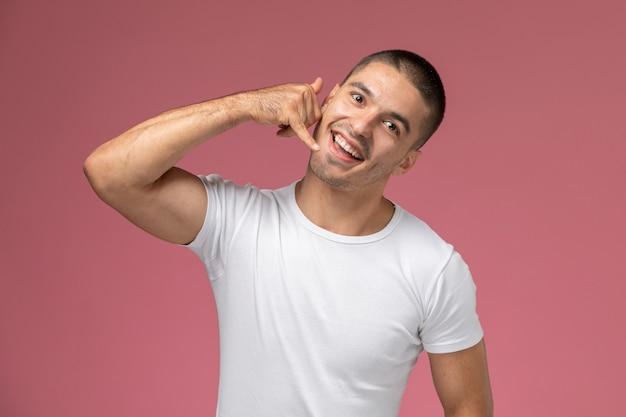 Jovem homem de camisa branca posando de frente para mostrar a ligação no fundo rosa