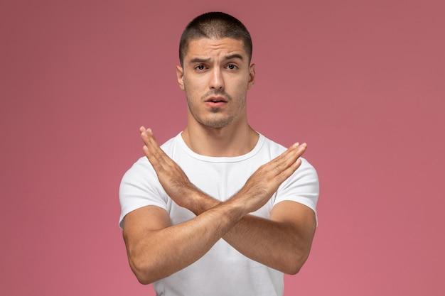 Jovem homem de camisa branca, vista frontal, mostrando sinal de proibição no fundo rosa