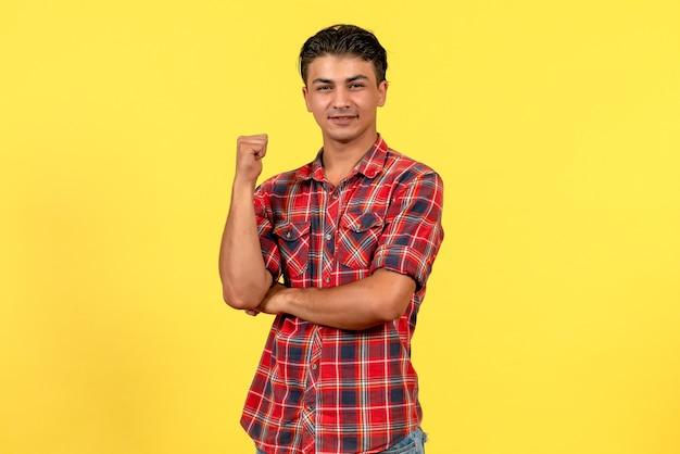 Jovem homem de camisa brilhante, de frente para a frente, posando no modelo masculino de mesa cor amarela