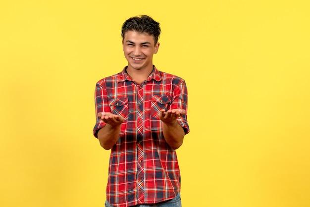 Jovem homem de camisa brilhante sorrindo de frente para o modelo masculino de cor de fundo amarelo