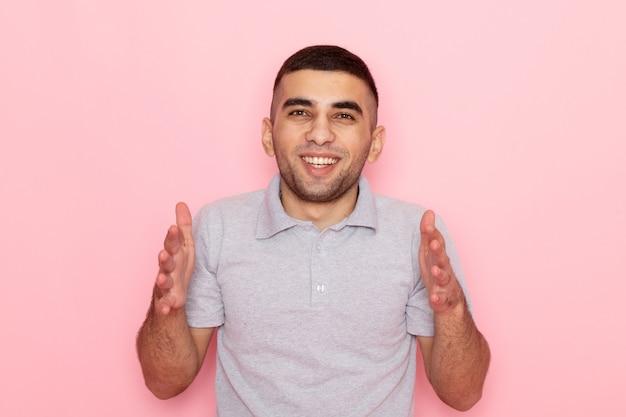 Jovem homem de camisa cinza posando com as mãos levantadas e um sorriso rosa