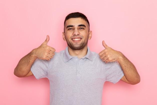 Jovem homem de camisa cinza posando e sorrindo de frente mostrando gestos horríveis na cor rosa