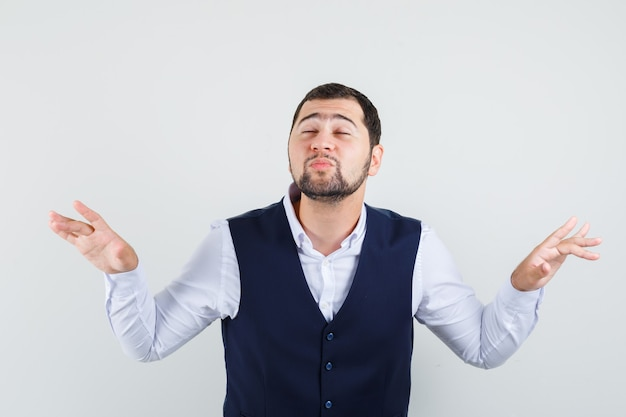 Jovem homem de camisa, colete levantando as mãos, fazendo beicinho, fechando os olhos e parecendo em paz