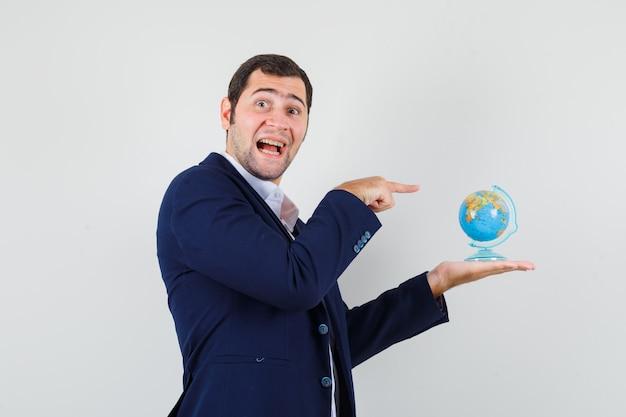 Jovem homem de camisa e jaqueta, apontando para o globo da escola e olhando alegre.