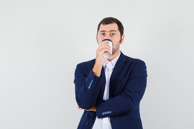 Jovem homem de camisa e jaqueta bebendo café e parecendo pensativo