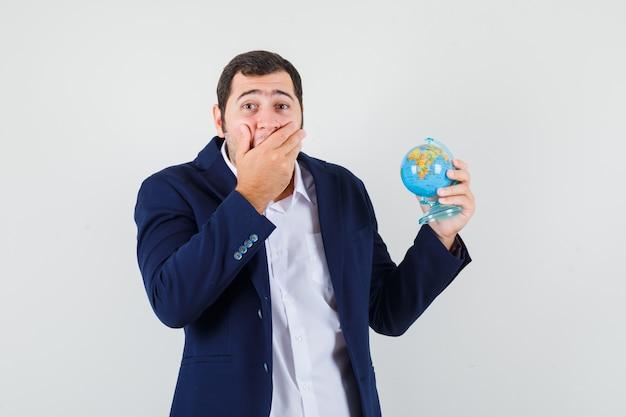 Jovem homem de camisa e jaqueta segurando o globo da escola e parecendo surpreso