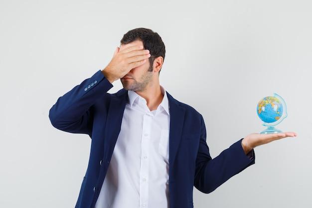 Jovem homem de camisa e jaqueta segurando o globo escolar, cobrindo os olhos com a mão