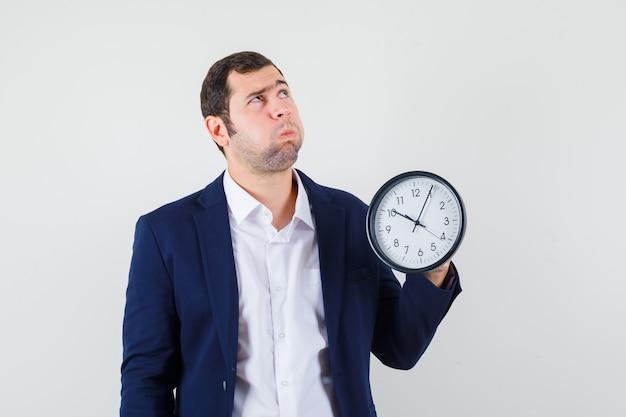 Jovem homem de camisa e jaqueta segurando um relógio de parede e parecendo pensativo