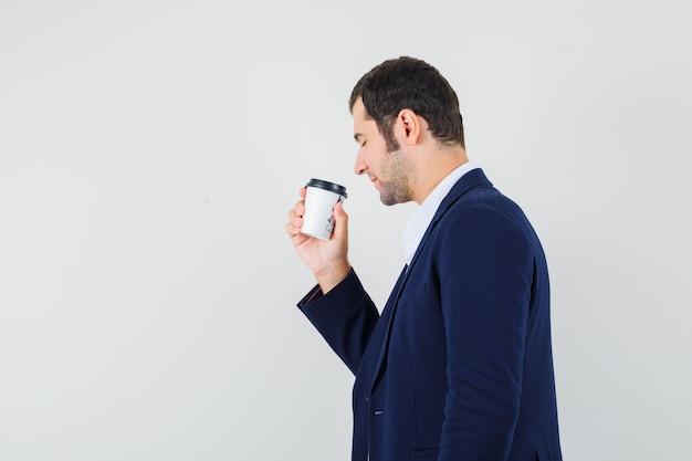 Jovem homem de camisa, jaqueta segurando uma xícara de café e parecendo encantado