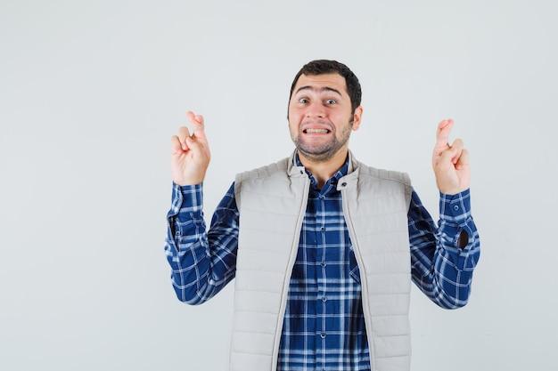 Jovem homem de camisa, jaqueta sem mangas em pé com os dedos cruzados e parecendo impaciente, vista frontal.