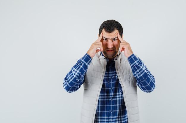 Jovem homem de camisa, jaqueta sem mangas, segurando os dedos na têmpora e parecendo preocupada, vista frontal.