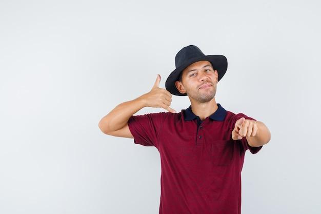 Jovem homem de camisa vermelha, chapéu preto mostrando me chama de gesto e olhando impaciente, vista frontal.