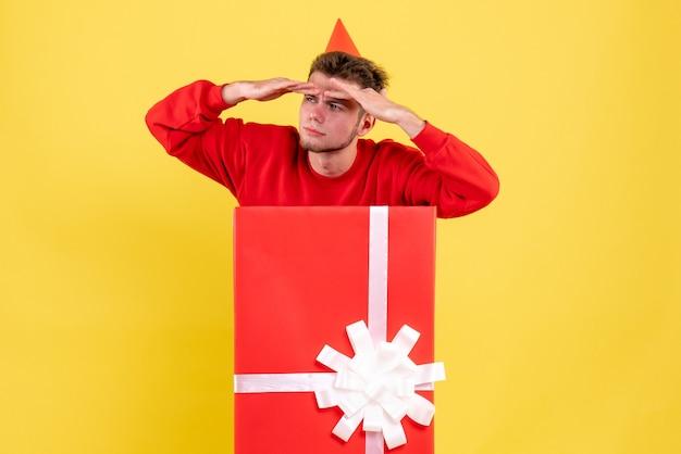 Jovem homem de camisa vermelha dentro da caixa de presente, vista frontal