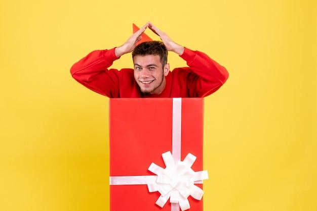 Jovem homem de camisa vermelha dentro da caixa de presente