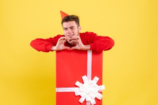 Jovem homem de camisa vermelha dentro de uma caixa de presente enviando amor