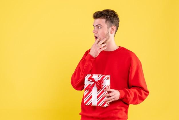 Jovem homem de camisa vermelha e presente de natal de frente