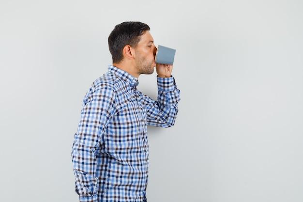Jovem homem de camisa xadrez tomando café