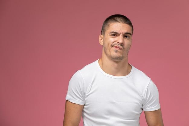 Jovem homem de camiseta branca, de frente para a frente, posando com uma expressão de descontentamento no fundo rosa