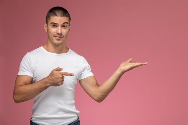 Jovem homem de camiseta branca posando e apontando para a frente na mesa rosa