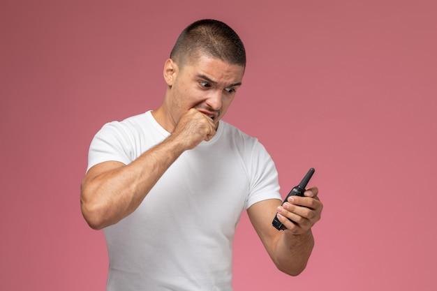 Jovem homem de camiseta branca usando walkie-talkie com expressão de raiva na mesa rosa
