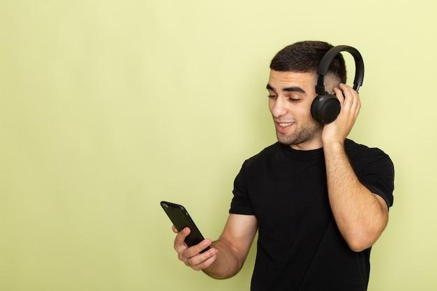 Jovem homem de camiseta preta segurando o telefone e ouvindo música no verde de frente