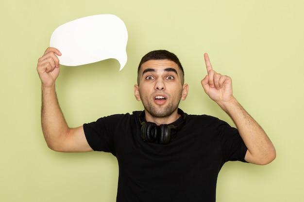Jovem homem de camiseta preta segurando uma placa branca com o dedo levantado em verde