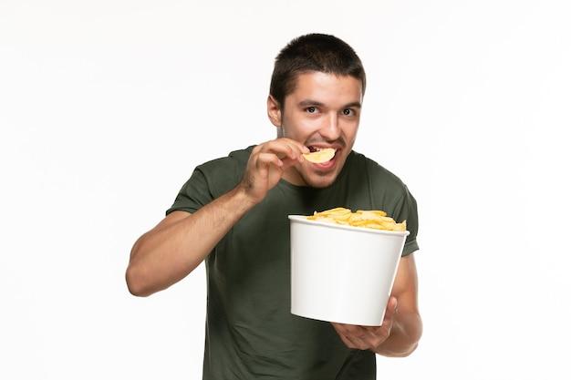 Jovem homem de camiseta verde segurando a cesta com batata cip e comendo na parede branca filme prazer solitário
