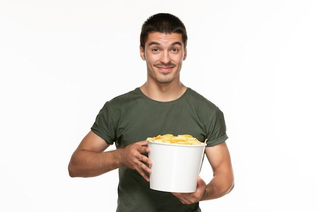 Jovem homem de camiseta verde segurando a cesta com batata cips e sorrindo na parede branca filme prazer solitário de frente