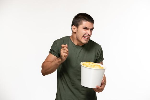 Jovem homem de camiseta verde segurando batata cips de frente assistindo filme na parede branca filme filme de pessoa solitária
