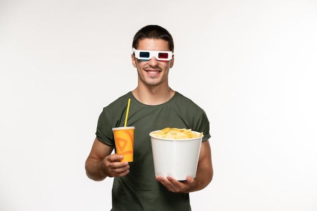 Jovem homem de camiseta verde segurando batata cips e refrigerante em d óculos de sol em filme de parede branca filmes solitários masculinos de frente