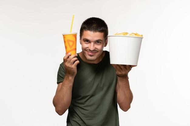 Jovem homem de camiseta verde segurando batata cips e refrigerante na parede branca filme cinema filmes solitários de vista frontal