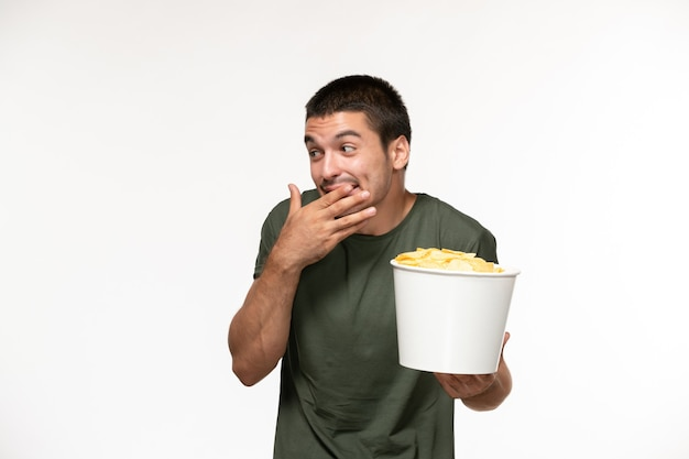 Jovem homem de camiseta verde segurando batata cips e rindo na parede branca filme solitário cinema pessoa de frente