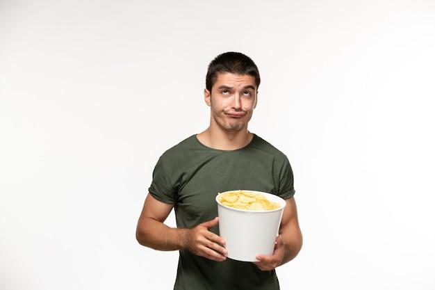 Jovem homem de camiseta verde segurando batatas cips de frente assistindo filme na parede branca clara pessoa filme solitário cinema