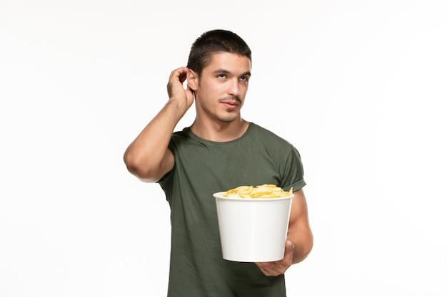 Jovem homem de camiseta verde, segurando batatas cips e assistindo filme na parede branca filme solitário, vista frontal