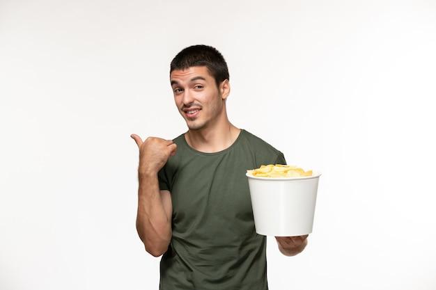 Jovem homem de camiseta verde segurando batatas cips na parede branca de frente.