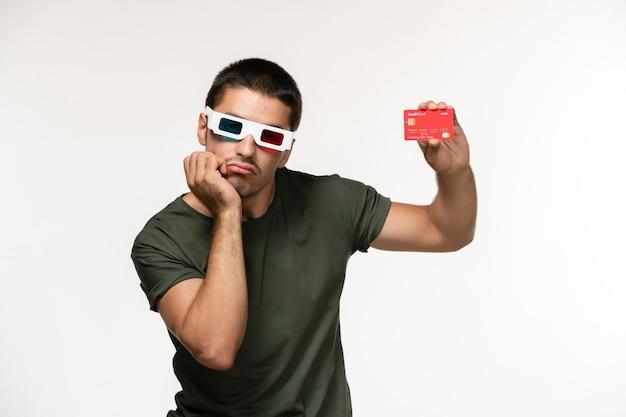 Jovem homem de camiseta verde segurando o cartão do banco vermelho em óculos de sol na parede branca filme de cinema solitário vista frontal