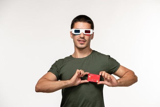 Jovem homem de camiseta verde segurando um cartão do banco vermelho em óculos de sol -d de frente para um filme de parede branco-claro cinema solitário