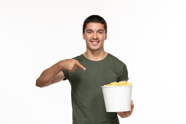 Jovem homem de camiseta verde segurando uma cesta com batata cip em uma parede branca filme prazer solitário vista frontal